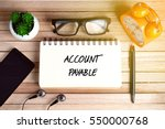 Small photo of Business Concept - Top view of smartphone, earphone, plant, eye glasses, alarm clock, pen and notebook written with ACCOUNT PAYABLE on wooden background.
