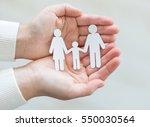paper cut family in hands  | Shutterstock . vector #550030564