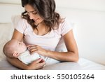 young mother with baby in bed | Shutterstock . vector #550105264
