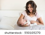 young mother with baby in bed | Shutterstock . vector #550105270