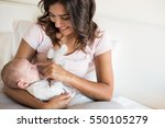 young mother with baby in bed | Shutterstock . vector #550105279