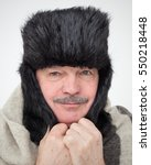 Small photo of Elderly man bundled up in fur hat and warm scarf. Very cold winter and unfavorable weather forecast.