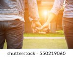 a young couple holding hands.... | Shutterstock . vector #550219060