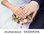 hands of bride and groom with...