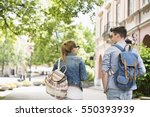 Stock photo rear view of young college friends talking while walking in campus 550393939