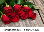 Stock photo red roses on a old wooden table 550407538