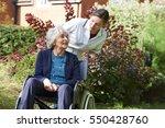 carer pushing senior woman in... | Shutterstock . vector #550428760