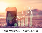 Business economic technology and freedom trader working concept. Smart phone on sand sunset beach double exposure graph money stock trading up trend arrow bar bokeh background. Vintage filter color