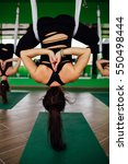 Small photo of young women making antigravity yoga exercises with a group of people. aero fly fitness trainer workout. white hammocks, eco green background studio. interior mirrors. upside down in the lotus position