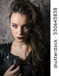 Small photo of Punk rock style or halloween make-up. Fashion woman model face with bright glamour makeup. Perfect skin, black gloss eyeshadows on eyes and dark brown glossy lips visage. Portrait close-up.