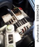 Small photo of close-up selective focus on small eco-car new electrical power alternator motor voltage generator installed with driving belt and electric plug and wiring under the hood of gasoline car engine