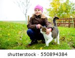 Stock photo little girl playing with cat in front of nature background 550894384