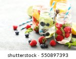Detox water in bottles with berries on wooden table - stock photo
