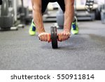 Small photo of Man using abdominal roller for working out abdominals. Front view. Focus on hands.