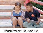 little girl and boy sitting using tablet outdoors in a park.