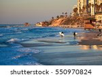 surfers at sunset in bat yam. | Shutterstock . vector #550970824