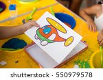a child draws with colored sand ... | Shutterstock . vector #550979578