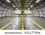 Small photo of Vintage old yellow war plane inside of a clean empty hangar