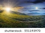 day and night concept image with path through a large meadow on the hillside in high mountains - stock photo