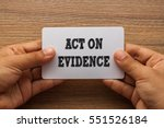 Small photo of ACT ON EVIDENCE written on white card holding with two hands