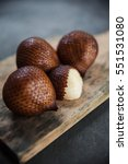 Small photo of Exotic tropical snake fruit. Four salak on wooden cutboard on shabby surface. Minimalistic vegan food still life.