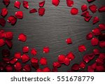Stock photo rose petals border background on a black slate stone plate for romantic designs 551678779