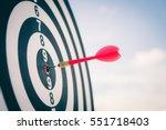 red dart arrow hitting in the... | Shutterstock . vector #551718403