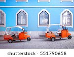Tuk tuk vehicle in front of blue facade building in the Lisbon, Portugal. Tuktuk is traditional taxi on Thailand and popular Turistic transportation at Lisbon. Travel photo scene.