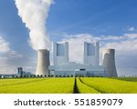 A shiny new lignite power station behind a rye field with wheel tracks leading to it - stock photo