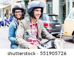 Small photo of Young woman with helmet sitting on pillion seat of Vespa in streets of Berlin
