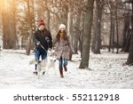 couple walking dog winter | Shutterstock . vector #552112918