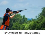 Small photo of Young man skeet shooting outdoors; shooting clay pigeon targets at gun club with airborne casing and copy space