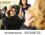 Small photo of Beautiful smiling blonde woman at hairdresser checking and fixing new curly hairdo with hand. Keratin restoration, latest trend, fresh idea, haircut picking, shorten tips, instrument store concept