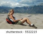 Woman sitting on sand dune - stock photo