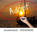 Small photo of Woman Hand Writing Adopt with a marker over transparent board. Isolated on Sunset Boat. Business concept. Stock Photo