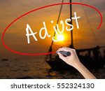 Small photo of Woman Hand Writing Adjust with a marker over transparent board. Isolated on Sunset Boat. Business concept. Stock Photo