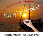 Small photo of Woman Hand Writing Studying Abroad? black marker on visual screen. Isolated on Sunset Boat. Education, technology, internet concept. Stock Image