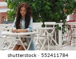 young woman at cafe using... | Shutterstock . vector #552411784