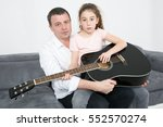 Small photo of Father and girl accomplice with a guitar at home