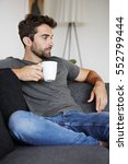 guy enjoying coffee on couch ... | Shutterstock . vector #552799444