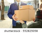 courier giving parcels to... | Shutterstock . vector #552825058