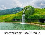 Small photo of Fountain with giant head spitting water into a pond at swarovski Kristallwelten in Wattens, Austria.