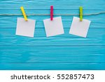 Stock photo blank pieces of note paper and colored clothespins isolated on blue three squares of blank paper 552857473