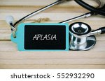 Small photo of Stethoscope and wooden tag written with APLASIA text. Medical conceptual.