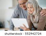 senior couple at home using... | Shutterstock . vector #552942724