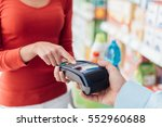 Small photo of Woman at the supermarket checkout, she is entering the security pin on the terminal, shopping and retail concept