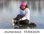 Small photo of Young girl on ice skates shoes take up.
