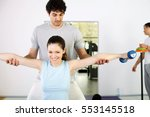 personal trainer assisting a... | Shutterstock . vector #553145518