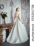 Small photo of Portrait of a beautiful fashion bride.Wreath with flowers on shiny blonde hair.Romantic girl in white elegant dress looking afar.