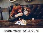 mother and daughter sitting in... | Shutterstock . vector #553372273